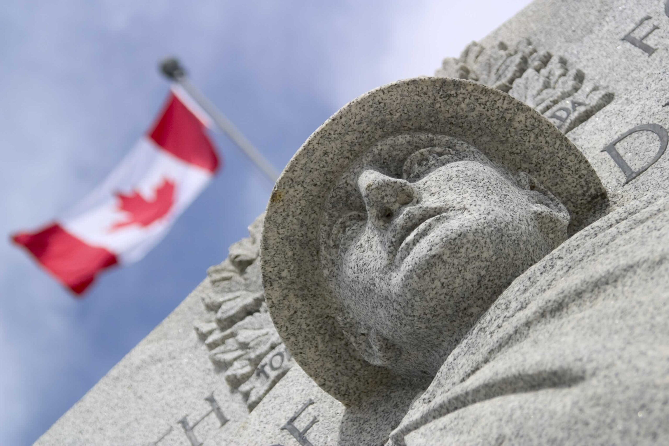 War monument with Canadian flag waving against graduated blue sky.