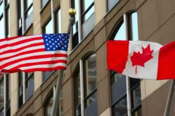 One U.S. and one American flag fly side-by-side against the backdrop of an office building