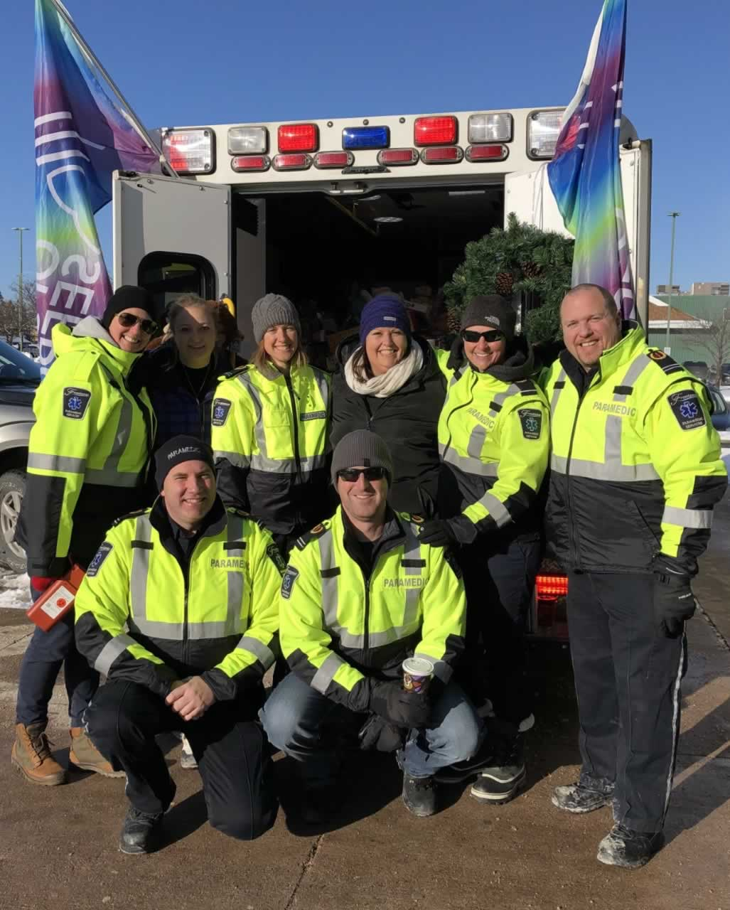 Group Photo of Local 462 Ambulance Communication Officers and Paramedics standing by ambulance