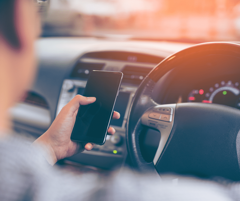 Person holding cellphone in the driver's seat of a vehicle