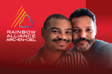 Two men close together smiling for the camera beside the Rainbow Alliance logo.